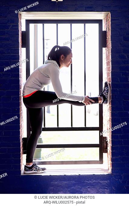 Woman Doing Stretching Near Window Of The Brick Wall