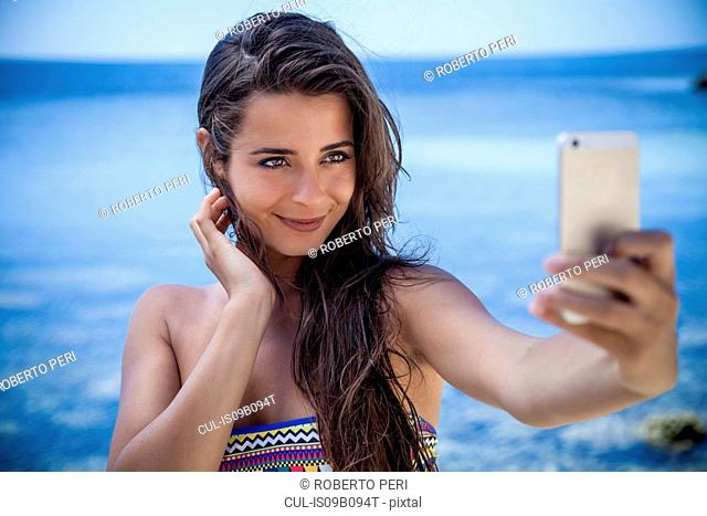 Beautiful young woman on beach taking smartphone selfie, Villasimius, Sardinia, Italy