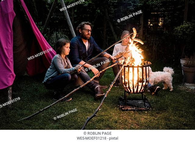 Man and two girls grilling sausage over camp fire in garden
