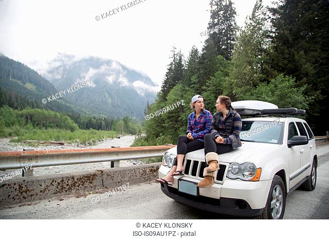 Hikers chatting on bonnet of vehicle, Lake Blanco, Washington, USA