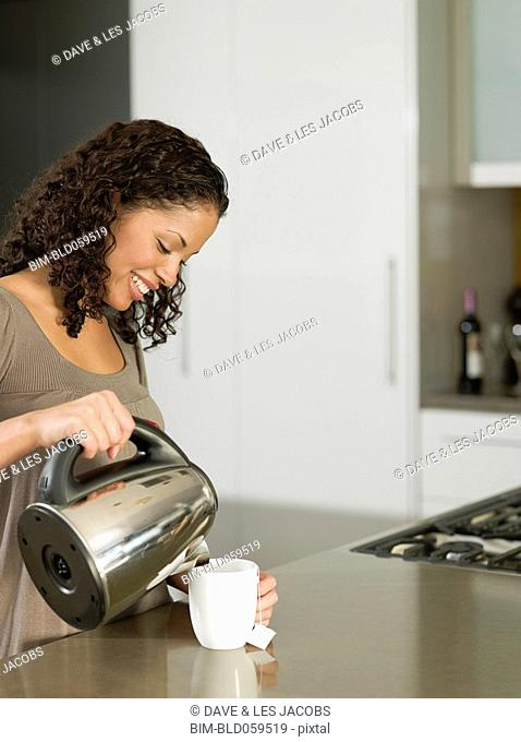 Mixed Race woman pouring tea