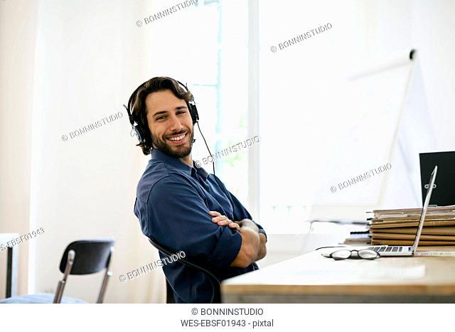 Businessman in office using headphones at desk