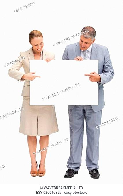 Smiling business people holding a poster