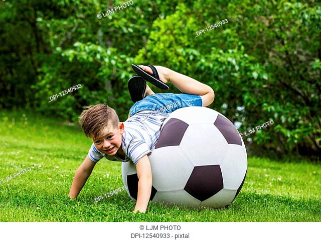 A young boy tumbling off the edge of a large ball while playing in a park on a warm summer day; Edmonton, Alberta, Canada