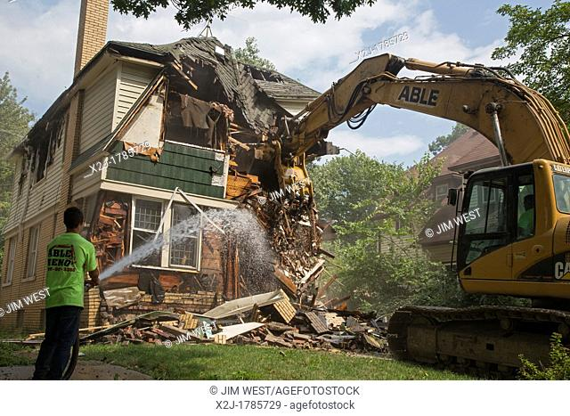 Detroit, Michigan - A fire-damaged and vacant home in the city's Morningside neighborhood is demolished  Detroit's population has crashed