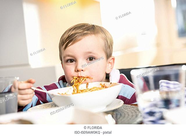 Portrait of messy boy eating spaghetti at lunch table