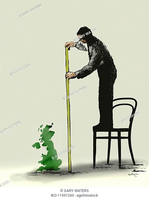 Man standing on chair measuring size of small United Kingdom