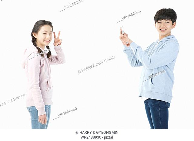 Side view of school girl and school boy posing and taking picture with smartphone smiling at front