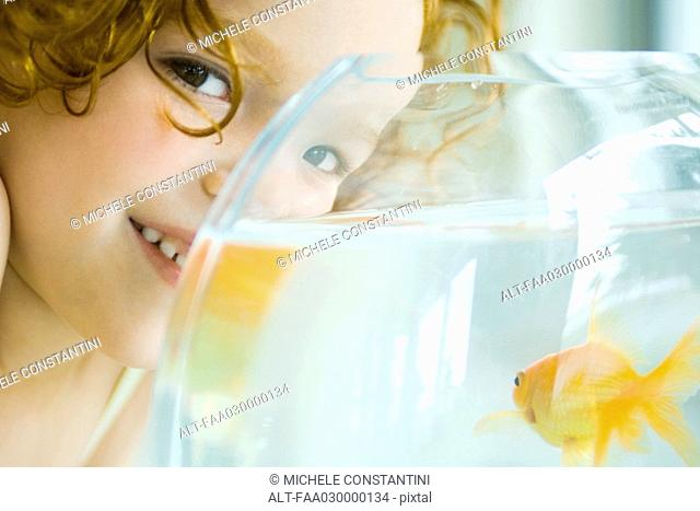 Girl with goldfish bowl, smiling at camera, close-up, cropped