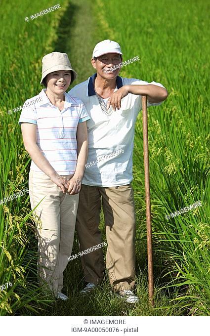 Farmer couple standing in rice field, man leaning on hoe