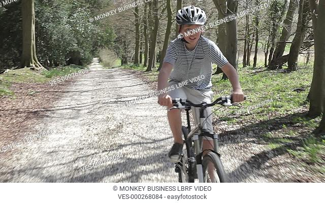 Boy cycling fast along country lane wearing safety helmet.Shot on Sony FS700 in PAL format at a frame rate of 25fps