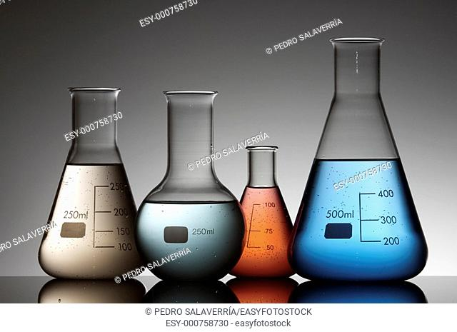 four laboratory flask with liquid inside multicolor