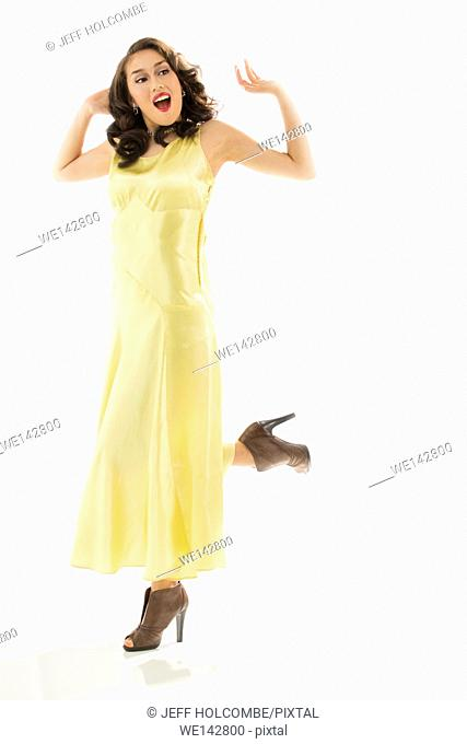 Beautiful young woman happy in vintage yellow dress, full length in brown heels, both arms raised
