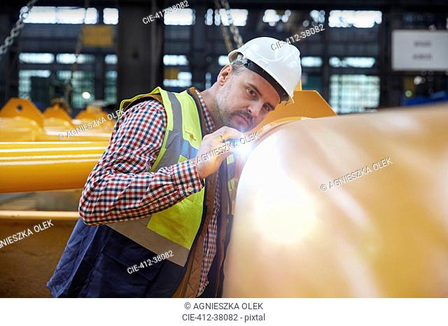 Focused male engineer with flashlight examining equipment in factory