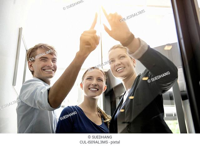 Businessman and businesswomen looking and pointing at light