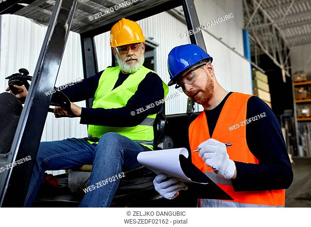 Man talking to worker on forklift in factory