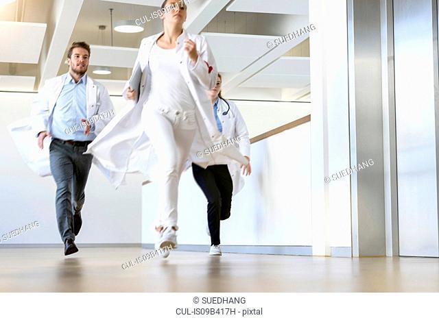 Male and female doctors running along hospital corridor