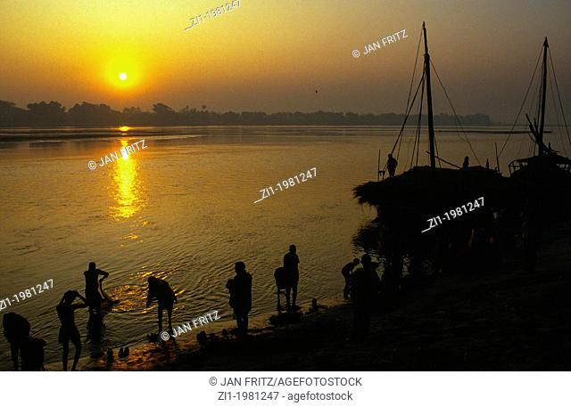 people at border of Mahanadi river at sunset, in Sonpur, India