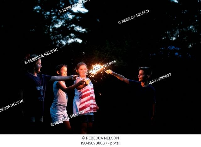 Boy and three girls igniting sparklers together at night on independence day, USA