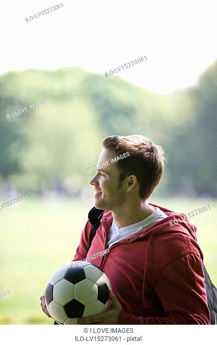 A young man in the park carrying a football