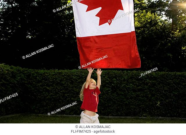 Little boy reaching for a Canadian flag, Toronto, Ontario