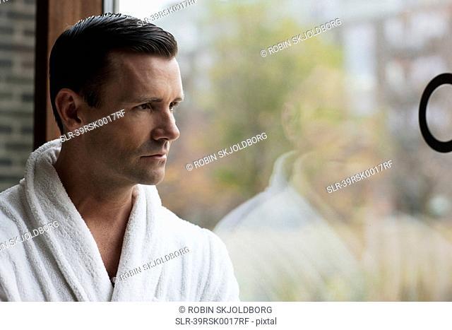 Man in bathrobe looking out window