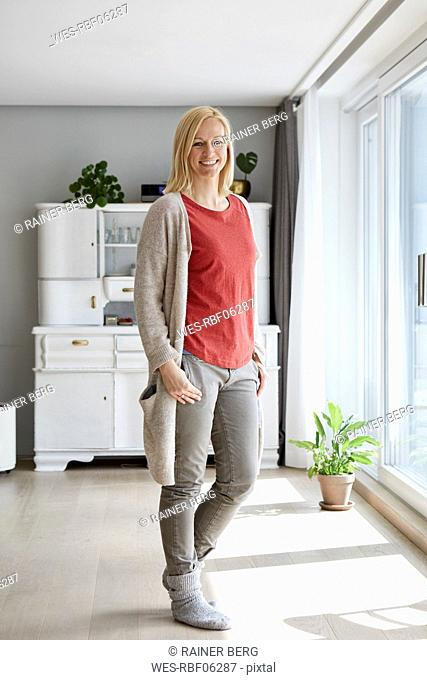 Confident woman standing in her comfortable home