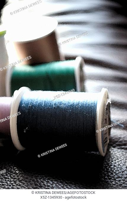 Several rolls of different colored thread with effects