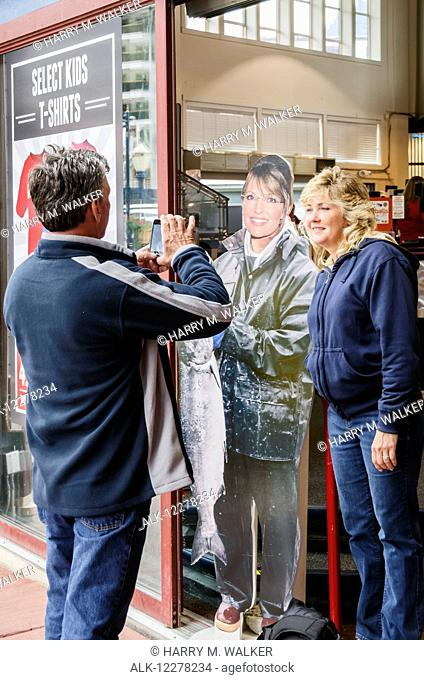Man photographing woman standing next to life-size cut out of Sarah Palin holding a salmon, Juneau, Southeast Alaska