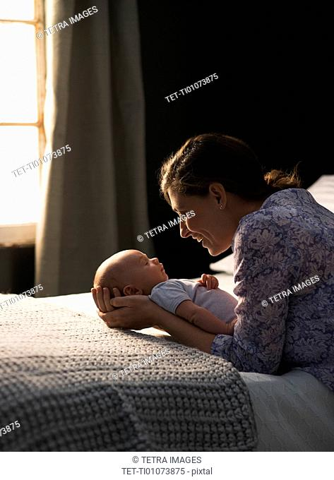 Mother holding baby boy (2-5 months) in bedroom