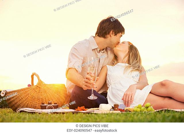 Attractive couple kissing on romantic sunset picnic