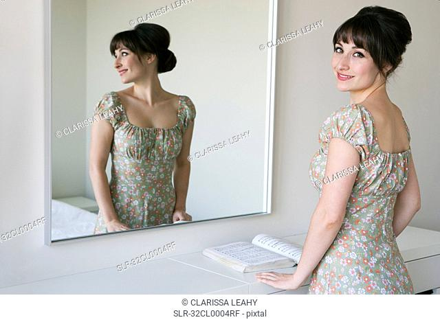Woman smiling in front of mirror
