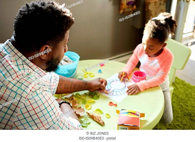 Father and daughter enjoying colouring in activity