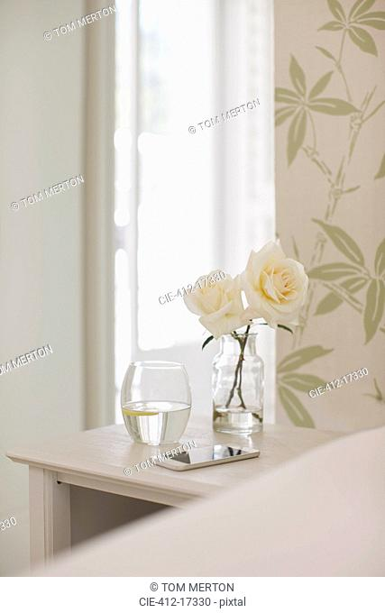 White roses on bedside table