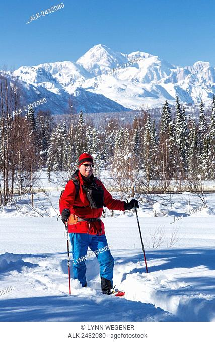 Man snowshoeing with the southside of Mt. McKinley in the background, Southcentral Alaska