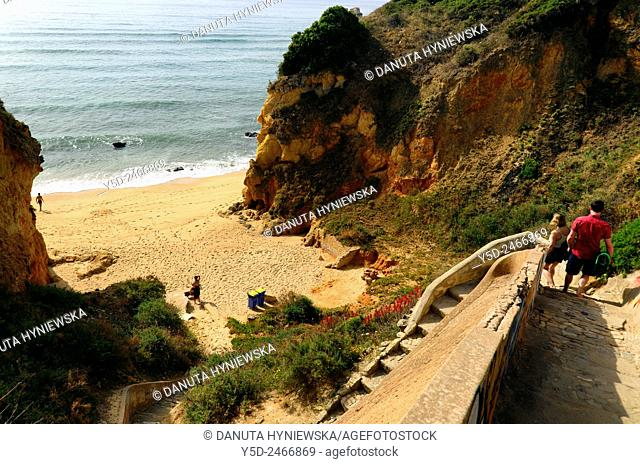 Europe, Portugal, Algarve, Western Algarve, Faro district, Lagos, young couple walking down to Pinhao beach