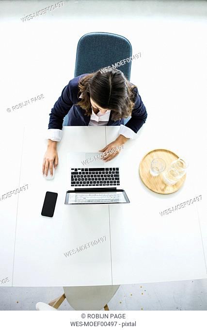 Businesswoman sitting at desk in the office working on laptop, top view
