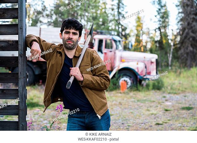 Young man holding axe, standing in front of a broken truck