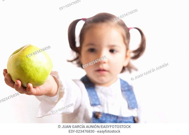 Portrait of happy girl holding a green apple. Isolated over white background