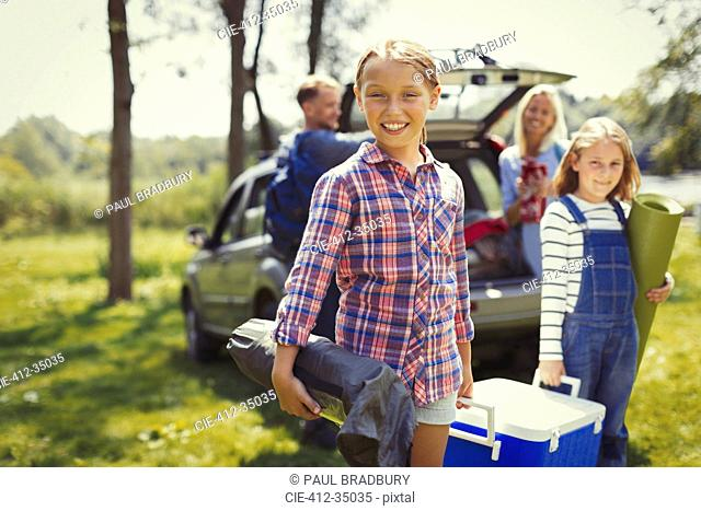 Portrait smiling family unloading camping equipment from car