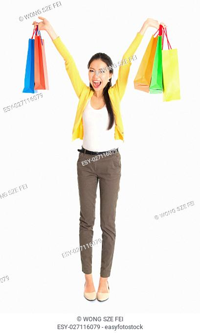 Happy young Asian woman shopper, hands outstretched holding shopping bags and smiling, full length isolated standing on white background