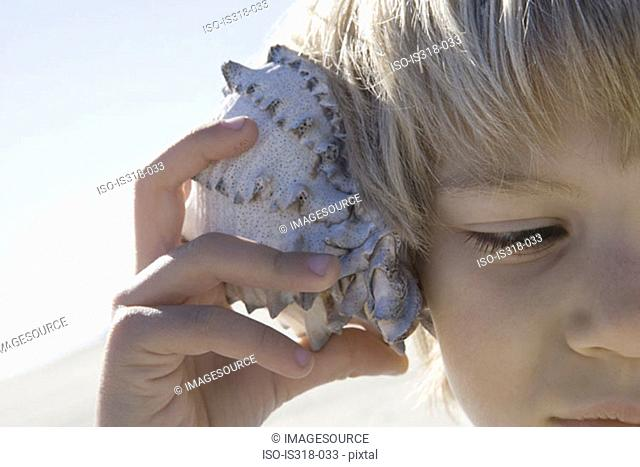 Boy holding shell to ear
