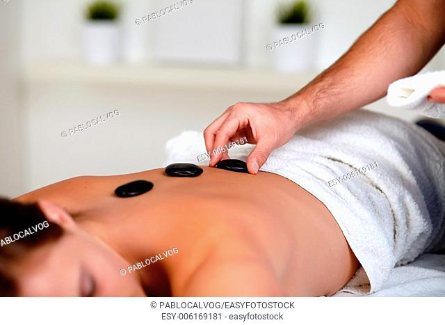 Close up portrait of a tired woman relaxing at a spa and receiving a hot stone massage