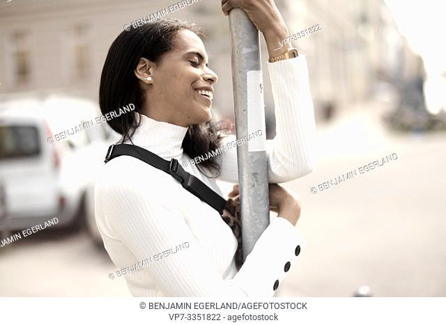 woman embracing street lamp post