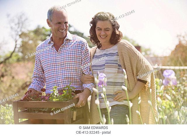 Smiling couple shopping for flowers in sunny plant nursery garden