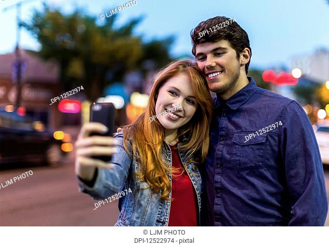 A young couple stand beside a city street at dusk taking a self- portrait with a smart phone; Edmonton, Alberta, Canada