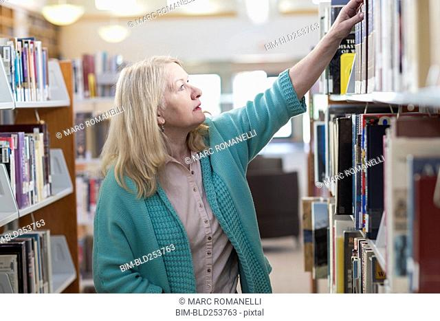 Curious Caucasian woman reaching for book in library