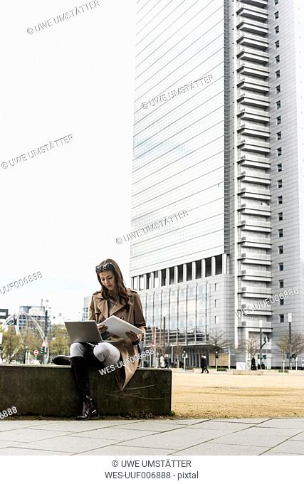 Young woman with laptop working outdoor