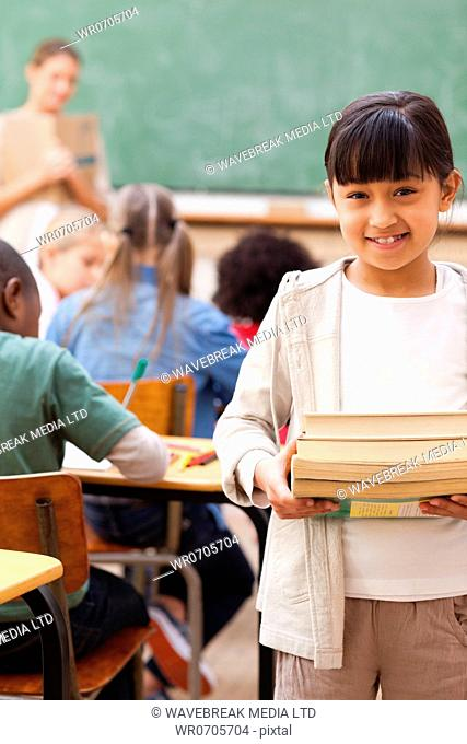 Smiling elementary student standing with pile of books