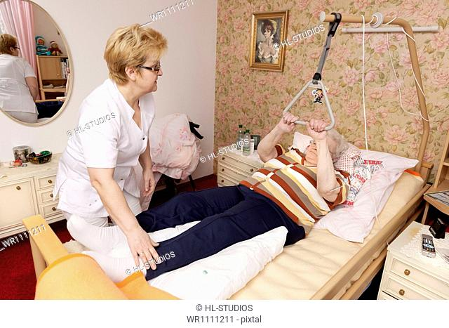 Geriatric nurse caring for old woman in bed